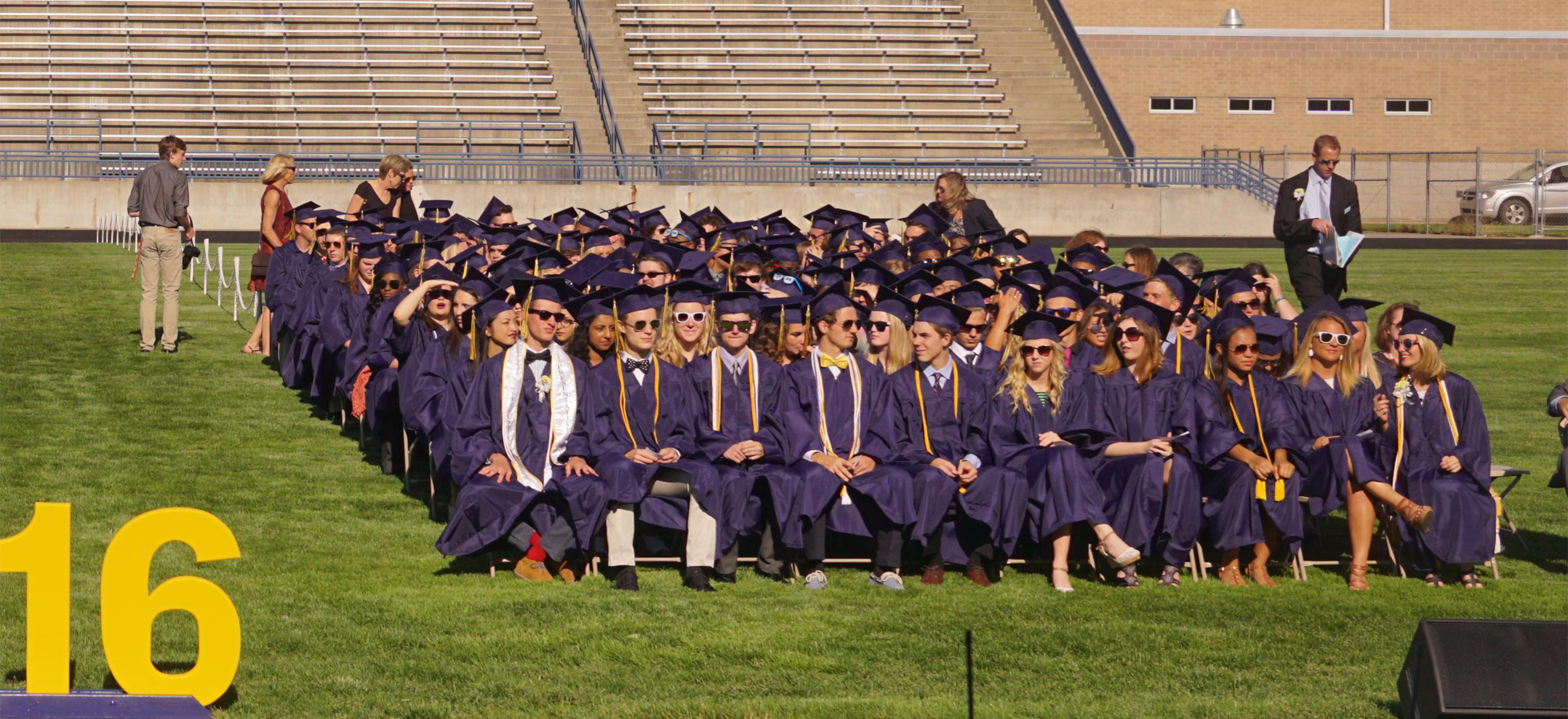 class of 2016 sitting in chairs in stadium with cap and gowns